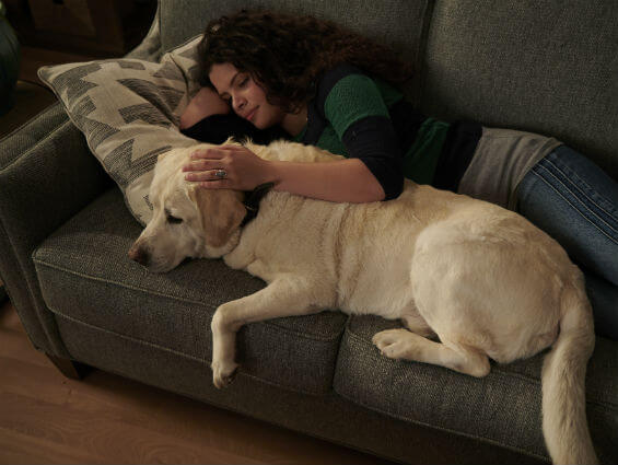 Girl with dog on sofa